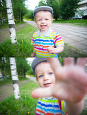 Baby boy walking in the park with funny face — Stock Photo