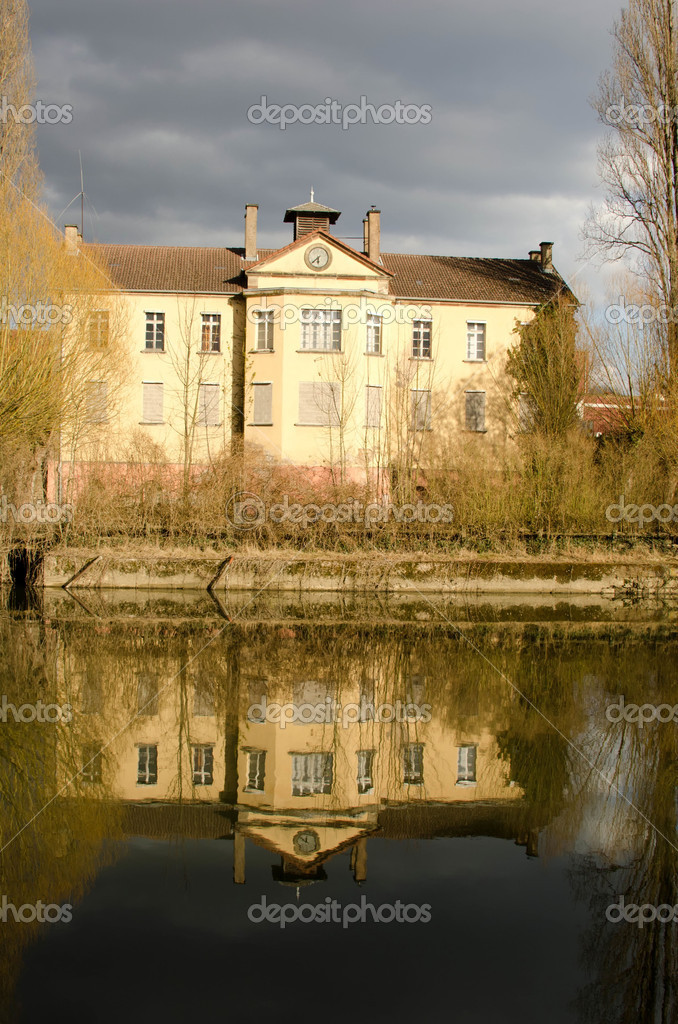 Two-storey mansion reflecting in water  Stock Photo #10740487