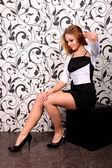 Young beautiful woman sitting on black pouf — Stock Photo