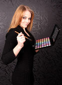 Woman with brush and eye shadows — Stock Photo