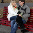 Stock Photo: Couple in love on bench with the rose