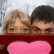 Young nice couple behind pink paper heart — Stock Photo
