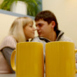 Lovely couple behind two yellow cups — Stock Photo