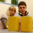 Stock Photo: Happy couple looking at two yellow cups