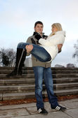 Young man carrying woman — Stock Photo