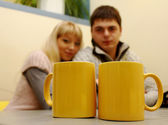 Happy couple looking at two yellow cups — Stock Photo