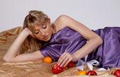 Beautiful blonde woman lying with fruits — Stock Photo
