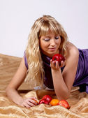 Pretty blonde girl looking at red apple — Stock Photo