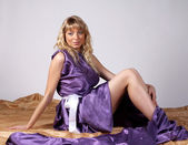 Beautiful blonde girl sitting on the floor in long purple dress — Stock Photo