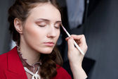 Beautiful young model getting fashion make-up — Foto Stock