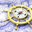 Stock Photo: Compass in ship's wheel over map
