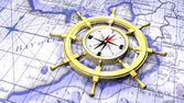 Compass in a ship's wheel over a map — Stock Photo