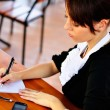 Female at the cafe calculating her budget and writing to notepad — Stock Photo