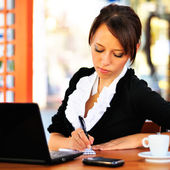 Businesswoman with laptop making some notes — Stock Photo