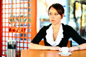 Lonely brunette at the cafe thinking about something sad — Stock Photo