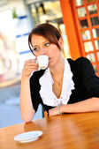 Attractive brunette drinks cappuccino at the cafeteria — Stock Photo