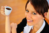 Close-up of smiley brunette holding a cup of coffee and looking — Stock Photo