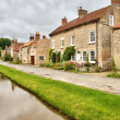 Quaint cottages and stream in an English village — Stock Photo