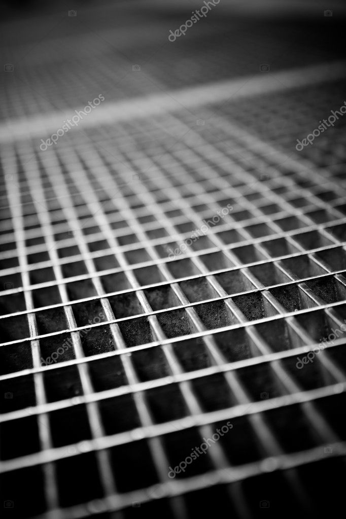 Black and white close up of a sidewalk subway grate with shallow depth of field.  Stock Photo #11447707