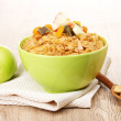 Tasty cornflakes in bowl with dried fruits and apple on wooden table - Stockfoto