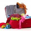 Open red suitcase with clothing isolated on a white — Stock Photo #10802213