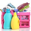 Stock Photo: Clothes with detergent in pink plastic basket isolated on white