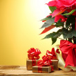 Beautiful poinsettia in flowerpot, gifts and ribbon on wooden table on yellow background — Stock Photo