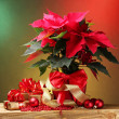 Beautiful poinsettia in flowerpot, gifts and Christmas balls on wooden table on bright background — Zdjęcie stockowe #10803187