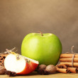 Cinnamon sticks,apples nutmeg and anise on wooden table on brown background — Stock Photo