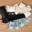 Cocaine in packages, dollars and handgun on wooden background - Photo