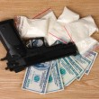 Cocaine in packages, dollars and handgun on wooden background - 