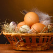 Chicken and quail eggs in a nest on wooden table on brown background - Stock Photo