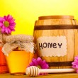 Sweet honey in barrel and jars with drizzler on wooden table on yellow background - Stock Photo