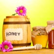 Sweet honey in barrel and jars with drizzler on wooden table on green background - Stock Photo