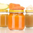 Jars of baby puree with spoon isolated on white — Stock Photo