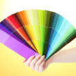 Hand holding bright palette of colors on yellow background — Stock Photo