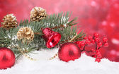 Christmas ball and green tree in the snow on red — Stock Photo