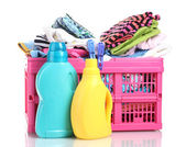 Clothes with detergent in pink plastic basket isolated on white — Stock Photo