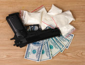 Cocaine in packages, dollars and handgun on wooden background — Stock Photo