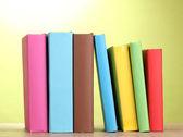 Livros ficar na mesa de madeira sobre fundo verde — Foto Stock