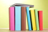 Livros com artigos de papelaria na mesa de madeira sobre fundo verde — Foto Stock