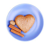 Heart-shaped cookie with cinnamon and nutmeg on saucer isolated on white — Stock Photo