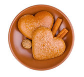 Heart-shaped cookies with cinnamon and nutmeg on saucer isolated on white — Stock Photo