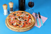 Aromatic pizza with wine on blue background — Stock Photo