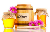Sweet honey in barrel and jars with drizzler isolated on white — Stockfoto