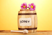 Sweet honey in barrel with drizzler on wooden table on yellow background — Stock Photo