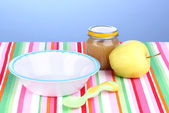 Jar of baby puree with plate and spoon on napkin on blue background — Foto Stock