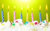 Beautiful birthday candles on green background — Stock Photo