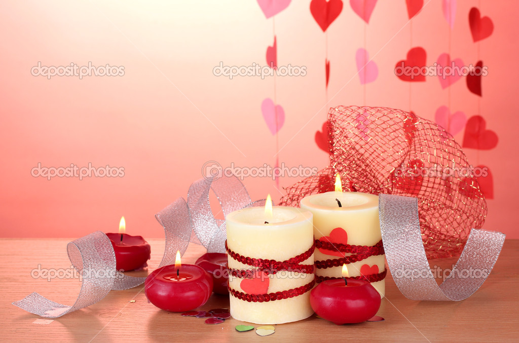 Candles for Valentine's Day on wooden table on red background — Stock Photo #10805056