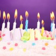 Birthday cake with candles on violet background — Stock Photo #10811621